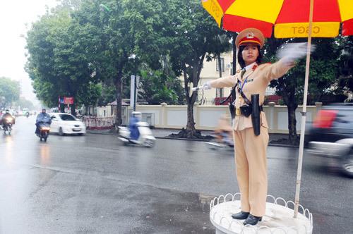 首都十字路口的女性交通交通交通部门为减少交通拥堵做出了贡献,并成为国际居民和朋友眼中的美丽形象:图片:Hoang Ha