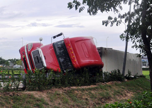 当高速公路穿过1号高速公路 - 东西高速公路时,集装箱卡车被翻车。照片:An Nhon