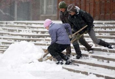 Women remove snow in the centre of the Siberian city of Krasnoyarsk October 26, 2006. The equivalent amount of snow that came down in all of October, fell on Thursday during twenty four hours, local media reported. REUTERS/Ilya Naymushin (RUSSIA)