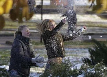 People play with first snow in Alexandrovsky Garden near Kremlin in central Moscow October 31, 2006. REUTERS/Sergei Karpukhin (RUSSIA)