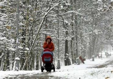 A woman pushes a pram at a snow covered park in Moscow October 30, 2006. Snow fell for the first time in Moscow this year on Monday. REUTERS/Viktor Korotayev (RUSSIA)