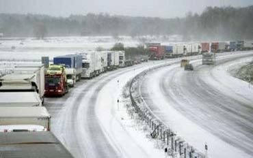 Haulage trucks, immobilised by a sudden snow storm and freezing temperatures, line a road near Enkoping in central Sweden November 1, 2006. SWEDEN OUT NORWAY OUT DENMARK OUT NO THIRD PARTY SALES REUTERS/Scanpix/Fredrik Sandberg (SWEDEN)