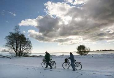A couple pushes their bicycles over a snow covered dyke on the island of Fehmarn in the Baltic Sea, November 2, 2006. REUTERS/Christian Charisius (GERMANY)