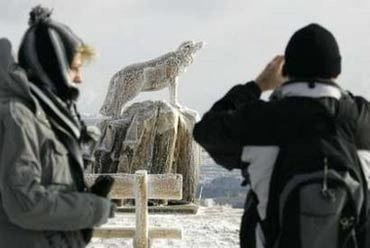 People take pictures of an ice covered sculpture at the Fichtelberg mountain after the first snowfall near the eastern German town of Oberwiesenthal at the German-Czech border November 2, 2006. REUTERS/Fabrizio Bensch (GERMANY)