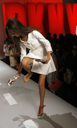 A model takes off her shoes while on the runway during the DKNY Spring 2008 collection show at New York Fashion Week September 9, 2007.