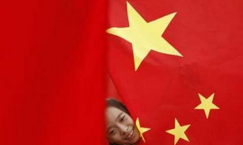 A girl plays amongst China's national flags put up by park officials to celebrate its National Day in Chaoyang park in Beijing September 30, 2007. China celebrates its National Day on October 1. REUTERS/Jason Lee