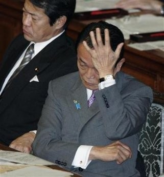 Japan's Prime Minister Taro Aso rests his head on his hand as he listens to a question next to Finance Minister Shoichi Nakagawa at the Lower House plenary session of the parliament in Tokyo November 18, 2008.