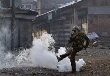 An Indian police kicks exploded tear gas shell thrown back by Kashmiri Muslim protesters during a protest in Srinagar, India, Friday, Dec. 26, 2008. Government forces on Friday clashed with hundreds of rock-throwing protesters after the main mosque in Indian Kashmir's biggest city opened for Friday prayers after seven weeks