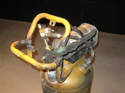 This undated photograph provided by the Covina, Calif. Police Department shows a device that suspect Bruce Pardo brought with him to the Knollcrest house where he allegedly shot and killed at least nine people. This photograph shows the tank from a compressor, below, where the actual compressor mechanism has been removed and replaced with