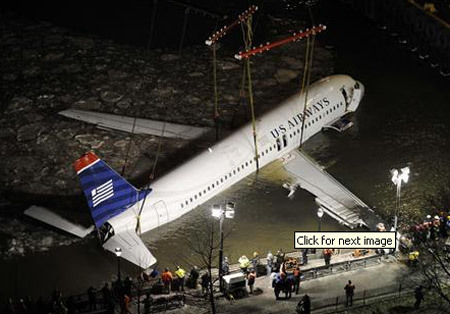 The wreckage of the US Airways airplane that crashed in the Hudson River emerges out of the river as emergency crew workers attempt to hoist it with a crane in New York, January 17, 2009.