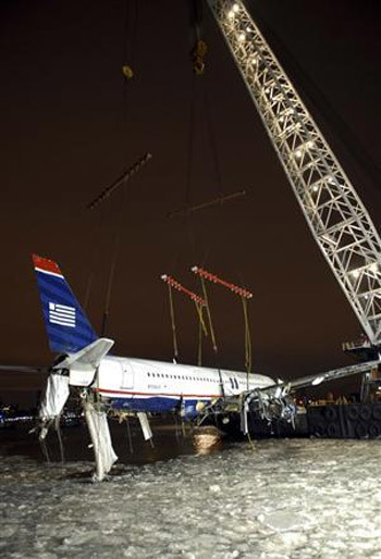 crane hoists the US Airways airplane, which crash landed in the Hudson River, onto a barge in New York January 17, 2009.