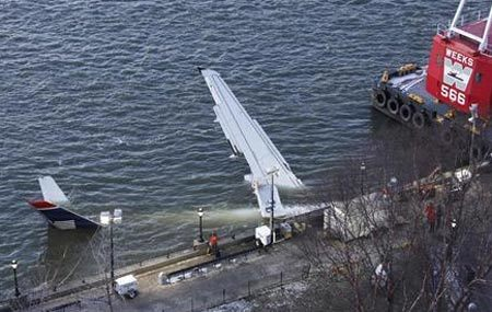 A heavy lifting crane sits on a barge next to the US Airways airplane which crashed in the Hudson River, as the wing sticks over the side of the seawall where the aircraft is secured awaiting removal, in New York January 16, 2009