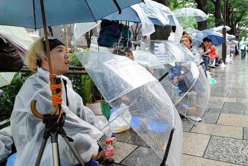 Người hâm mộ xếp hàng chờ mua iPhone 4 bất chấp trời mưa. Ảnh: AFP