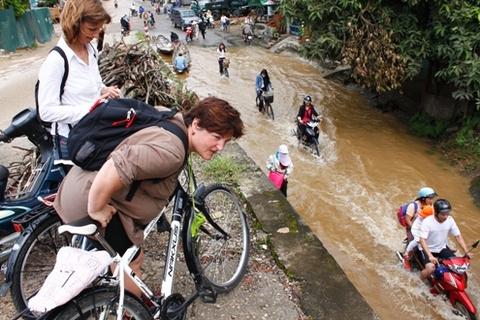 """Hai vị khách nước ngoài đạp xe đi """"tham quan"""" lụt ở Huế."""