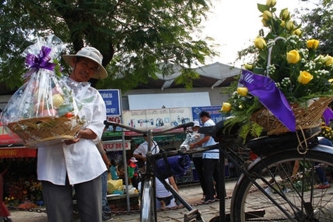 Những người làm nghề xe thồ đều không nề hà bất cứ món hàng hóa nào. Trong ảnh: một lão xe thồ đang hối hả cếp hàng vòng hoa và đồ cúng…
