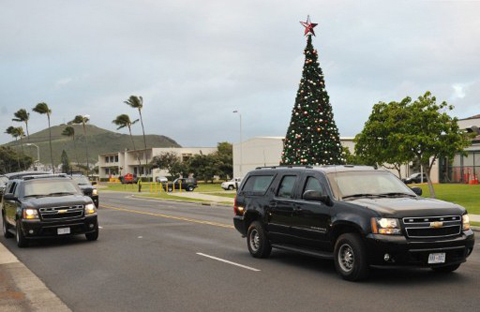 The motorcade carrying US President Barack Obama drives past a Chirstmas tree on Marine Corps Base Hawaii December 24, 2011. Obama spent part of the day playing golf with friends at the course on the base.