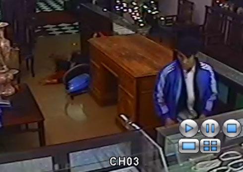 Hình ảnh tên sát nhân sau khi gây án, cố dùng cùi tay đập kính vơ vét vàng. Ảnh cắt từ clip.