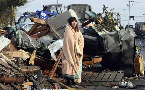 Yuko Sugimoto, wrapped in a blanket, scours the tsunami wreckage for her missing son in Ishinomaki, Miyagi prefecture
