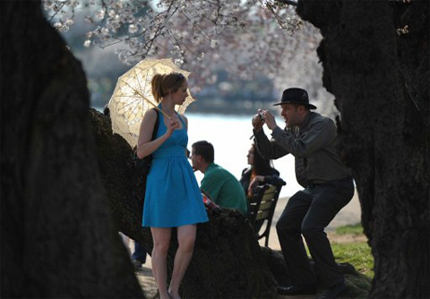 UNITED STATES, Washington : TOPSHOTS - A couple take photos beneath cherry blossom trees adjacent to the Tidal Basin on the National Mall in Washington, DC, on March 17, 2012. The iconic trees are beginning to bloom, with the National Park Service forecasting peak bloom between March 20 and 23, one of the earliest years on record due to warmer than average temperatures. TOPSHOTS / AFP PHOTO / MLADEN ANTONOV