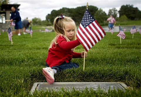 Mackenzie Griffith, 3, decorates a grave with a flag in honor of Memorial Day at Riverside National Cemetery, in Riverside County, Calif., on Saturday, May 26, 2012. Griffith was with a group of Orange County volunteers and her grandfather, a World War II veteran, R.V. Scott, is also buried there. AP