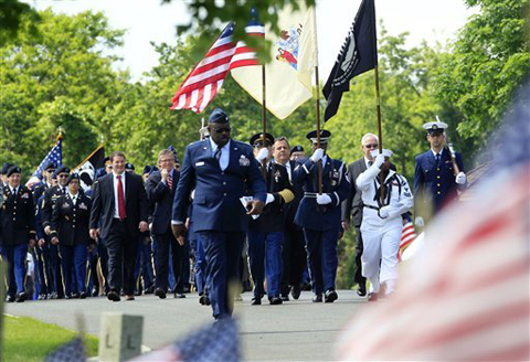 New Jersey Gov. Chris Christie, center, walks behind an honor guard during Memorial Day ceremonies at Brig. General William C. Doyle Veterans Memorial Cemetery in Wrightstown N.J., Saturday, May 26, 2012.AP
