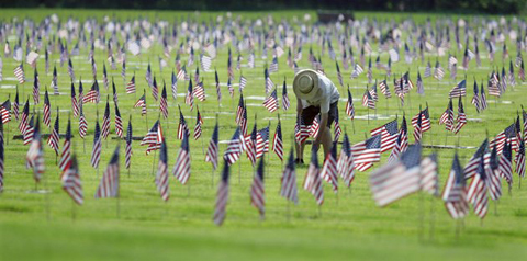 A man uprights a fallen flag at graves of military personnel and their families before Memorial Day ceremonies at Brig. General William C. Doyle Veterans Memorial Cemetery in Wrightstown N.J., Saturday, May 26, 2012.AP