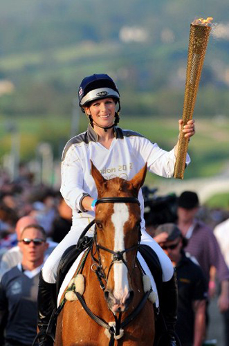 Zara Phillips, granddaughter of Britain's Queen Elizabeth II, carries the 2012 London Olympic Flame at Cheltenham Racecourse in central England, on May 23, 2012. The 2012 London Olympics begins on July 27, 2012