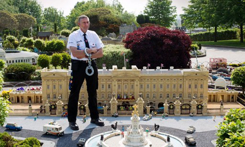 Security guard Bob Chapplegroves poses for pictures with a lego model of Buckingham Palace in London, on May 24, 2012, containing a 10cm high lego figure of Britain's Queen Elizabeth II, complete with a real diamond-encrusted crown. The Queen's Diamond Jubilee will take place June 2-5, 2012, and celebrations will include a festival of boats on the river Thames and the lighting of more than 2,000 beacons around the country during a four-day public holiday.