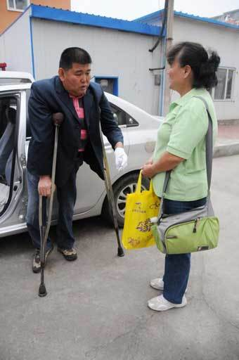 Bai Jindou, a disabled driver, talks with a woman whose child took part in this year's National College Entrance Exam in Harbin, Northeast China's Heilongjiang province, on June 7. Bai is the vice-chairman of a disabled drivers' association and his team has been picking up disabled candidates since 2011. [Photo/Xinhua]