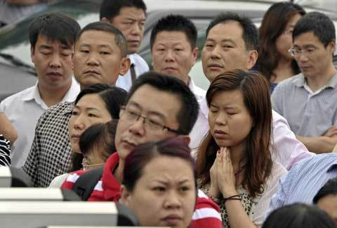 A parent prays outside a high school as parents wait for students during the first test of the National College Entrance Exams in Nanjing, Jiangsu province June 7, 2012. [Photo/Agencies]