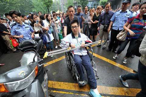 A candidate with a leg injury is wheeled into an examination hall in Nanjing, Jiangsu province on June 7, 2012. [Photo/Xinhua]