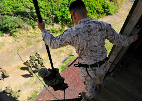 Corporal Jerel Bersolona (right), Rappel Master from 1st Battalion, 3rd Marines in Hawaii, helps members from 2nd Battalion Princess Patricia's Canadian Light Infantry from Shilo, Manitoba, practices Fast Rope Insertion Extraction System, at Marine Corps Base Hawaii, Honolulu, Hawaii, on July 2 2012.