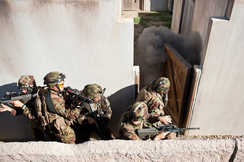 Soliders from Alpha Company, New Zealand Army, conduct urban combat training at the Bellows Air Force Station training facility. Personnel from their host unit, 1st Battalion, 3rd Marine Regiment, played the role of enemy party for the simulation.