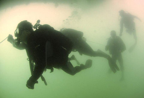 Royal Australian Navy divers, participating in Rim of the Pacific (RIMPAC) 2012, swims under the battleship USS Missouri (BB-63), as part of a familiarization dive with Mobile Diving and Salvage Unit 1 Navy divers, whom are also participating in RIMPAC.
