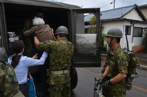 A handout photograph dated 12 July 2012 provided by the Japan Self Defense Forces shows self defense forces personnel helping a victim in the flooded streets in Aso city, Kumamoto prefecture, Japan. Ảnh: EPA