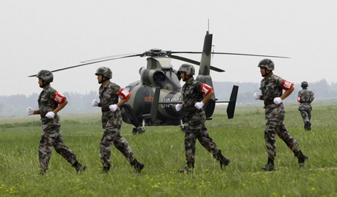 Soldiers run past a Z-9WZ military helicopter designed and manufactured by China during a media visit at the military base of Chinese People's Liberation Army Army Aviation 4th Helicopter Regiment, on the outskirts of Beijing, July 24, 2012, ahead of Army Day on August 1. [Photo/Agencies]