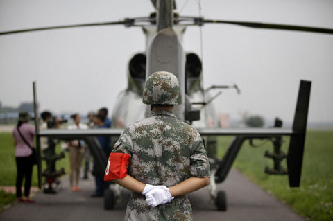 A soldier stands guard behind a Z-9WZ military helicopter designed and manufactured by China during a media visit at the military base of Chinese People's Liberation Army (PLA) Army Aviation 4th Helicopter Regiment, on the outskirts of Beijing, July 24, 2012, ahead of Army Day on August 1.[Photo/Agencies]