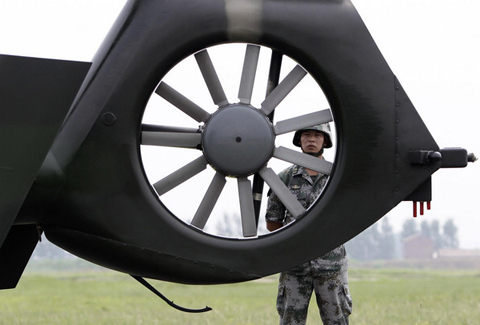 A soldier stands guard next to a Z-9WZ military helicopter designed and manufactured by China during a media visit at the military base of Chinese People's Liberation Army Army Aviation 4th Helicopter Regiment, on the outskirts of Beijing, July 24, 2012, ahead of Army Day on August 1. [Photo/Agencies]
