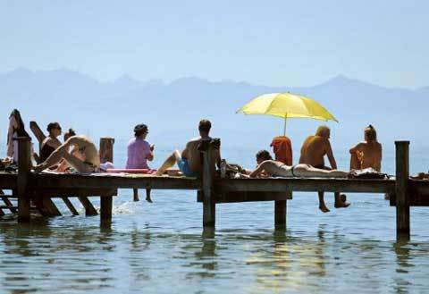 People lie under a sun shade and sunbath on a bathing jetty on lake Starnberger See in Bavaria, southern Germany on August 19, 2012. Temperatures reached a record high this weekend of August 19, 2012 throughout Germany.