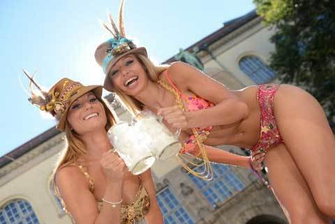 German models Nina Eckert (L) and Rebecca Fiedler (R) wearing a feathered cap and swim suits by Glam Beach Wear designer Pia Bolte, pose with ice cream filled beer mugs in Munich, southern Germany on August 19, 2012. Temperatures have reached a record high this weekend throughout Germany.