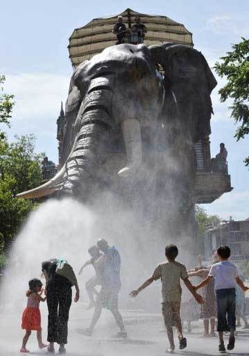 A 12-metre high mechanical elephant, made of steel and wood, sprays water from its trunk over children and adults on August 19, 2012, at the site of Les Machines de L'ile on the Ile de Nantes, a five-kilometre long, one-kilometre wide island in the centre of the city of Nantes, western France