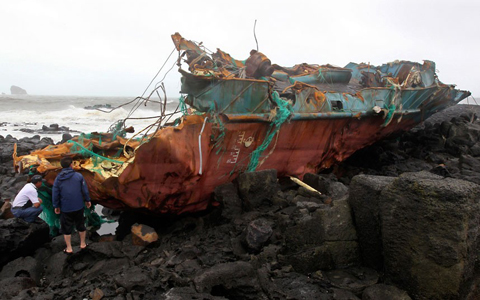 The wreckage of a Chinese ship is washed up onto the shore after it slammed into rocks off the coast of Jeju