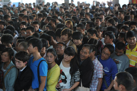 "Thousands of travellers queue up at a railway station in Hefei, east China's Anhui province on September 29, 2012, to catch trains ahead of the National Day holidays. Millions of Chinese are travelling home for holidays during the ""golden week"" break as China celebrates National Day on October 1"