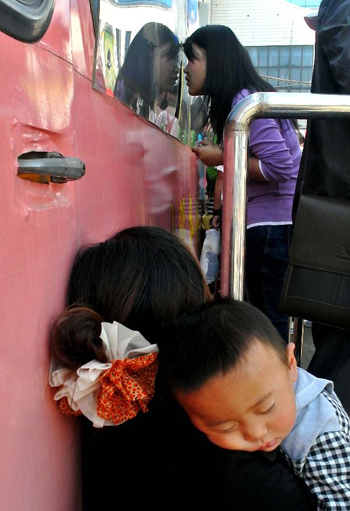 A parent holding a child asleep rests besides a ticket office at Zhengzhou Railway Station in Zhengzhou, capital of central China's Henan Province, Sept. 29, 2012. During the Mid-Autumn Festival and Chinese National Day festival, which will last from Sept. 30 to Oct. 7, Zhengzhou Railway Station is expected to send 1.2 million passengers, 3.2% more than the same period last year