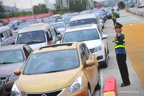 A staff member guides vehicles at a tollgate in Wuhan, capital of central China's Hubei Province, Sept. 30, 2012. More than 660 million people are expected to travel during the week-long Mid-autumn festival and National Day holiday starting Sept. 30, an increase of 8.8 percent from the same period last year, according to the Ministry of Transport.