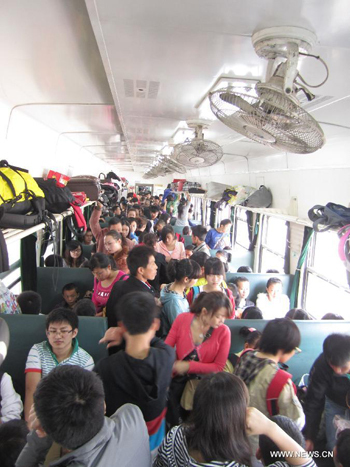 Passengers are seen on a train from Guiyang to Yuping, southwest China's Guizhou Province, Sept. 30, 2012, the first day of an eight-day holiday. Authorities predict that around 740 million trips will be made by Chinese people during the vacation that combines the National Day Holiday and the Mid-Autumn Festival.