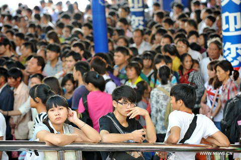 Passengers wait at a long-distance coach terminal in Nanning, capital of south China's Guangxi Zhuang Autonomous Region, Sept. 30, 2012. Authorities predict that around 740 million trips will be made by Chinese people during the vacation that combines the National Day Holiday and the Mid-Autumn Festival.