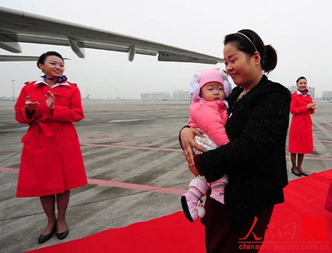 Luo Wei, a deputy to the 18th National Congress of the Communist Party of China from Sichuan, is going to board the plane to Beijing to attend the Congress with her five-month-old daughter.