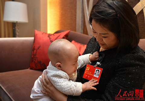 Luo Wei, a deputy to the 18th National Congress of the Communist Party of China, takes care of her five-month-old daughter in a hotel after a group discussion in Beijing on Nov. 10, 2012. Luo, who took her baby to Beijing as she is still breastfeeding, is the youngest deputy of Sichuan province delegation. She donated 55 percent of her liver to save the life of an unrelated person in 2005.