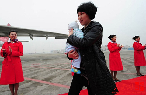 Jiang Min, a deputy to the 18th National Congress of the Communist Party of China from Sichuan, is going to board the plane to Beijing to attend the Congress with her four-month-old daughter
